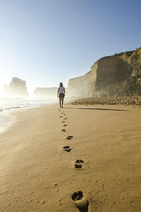 Mujer pasea por la orilla del mar